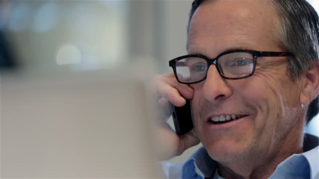 vídeos y material grabado en eventos de stock de confident older businessman talks on phone excitedly with client (dolly shot) - hablar