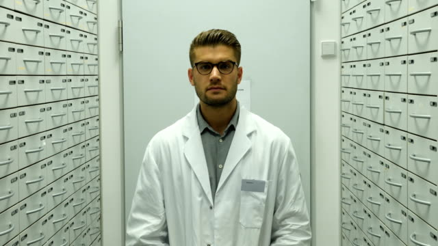 confident pharmacist in storage room of pharmacy - lab coat stock videos & royalty-free footage
