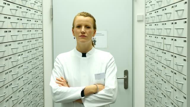 confident pharmacist smiling in storage room - scienziata video stock e b–roll