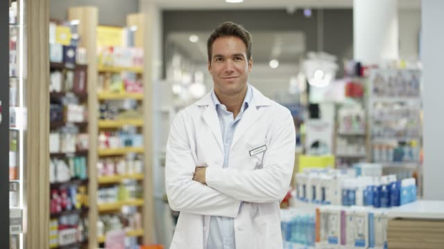 confident pharmacist with arms crossed at pharmacy - waist up stock videos & royalty-free footage
