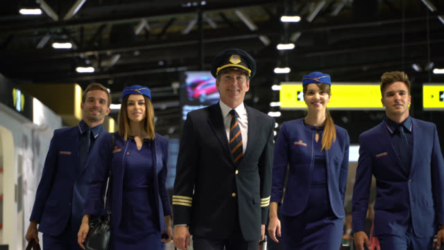 confident pilot and cabin crew walking through airport ready to work - crew stock videos & royalty-free footage