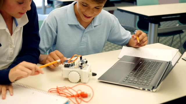Confident private high school STEM students test robot in engineering class