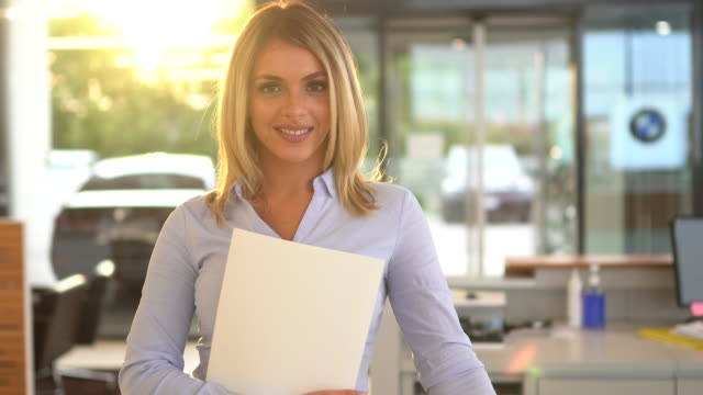 vidéos et rushes de vendeuse confiante dans la salle d'exposition de voiture - vendeur