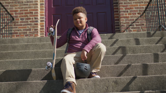 slo mo confident school boy holding a skateboard and helmet looks at camera while sitting on stair case - rucksack stock videos & royalty-free footage