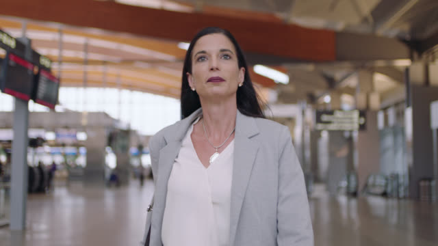 confident senior businesswoman walks through lively airport terminal. - geschäftsreise stock-videos und b-roll-filmmaterial