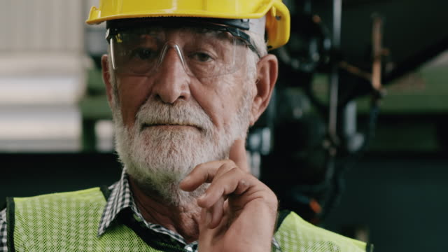 confident senior industrial worker portrait. slowmotion, caucasian male, overalls, helmets. industrial and manufactory concept. - stereotypically working class stock videos & royalty-free footage