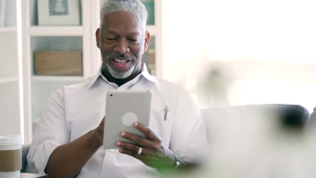 confident senior man looks at digital tablet at home - solo un uomo anziano video stock e b–roll