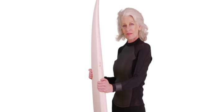 confident senior woman in wetsuit holding surfboard smiling at camera in studio - old diving suit stock videos and b-roll footage