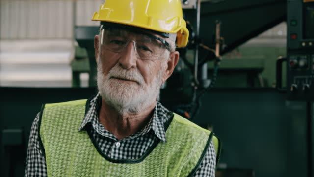 vidéos et rushes de verticale confiante de travailleur industriel aîné de sourire. slowmotion, mâle caucasien, salopettes, casques. concept industriel et manufactory. - non us film location