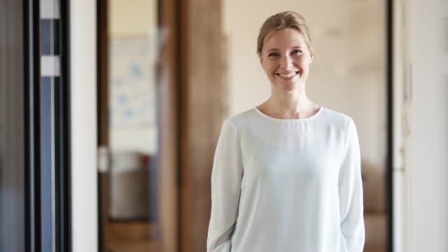 vidéos et rushes de femme d'affaires de sourire confiant dans le bureau - trentenaire