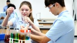 Confident STEM school students conducting chemistry experiment