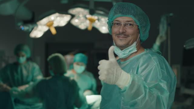 vídeos y material grabado en eventos de stock de cirujano seguro mostrando los pulgares hacia arriba en el quirófano - quirófano