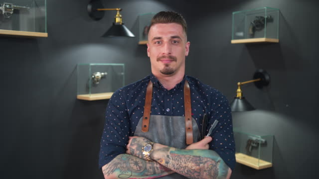 confident tattooed barber at his barber shop - beauty salon stock videos and b-roll footage