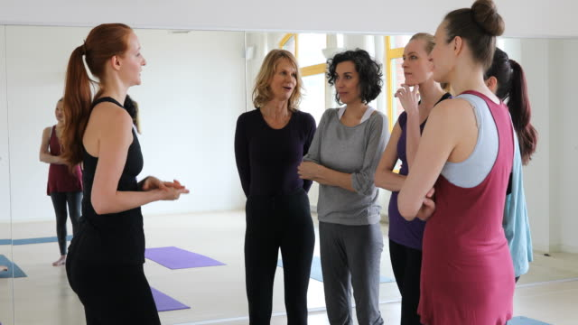 Confident trainer talking to women at yoga class