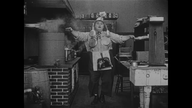 1918 confident waiter (buster keaton) dances his way into kitchen provoking chef (fatty arbuckle) to dance wearing the pots and pans - chef stock videos and b-roll footage