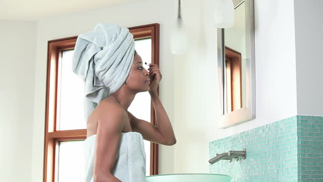 Confident woman applying makeup in bathroom mirror