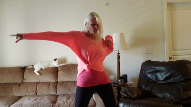 confident woman dances in her house while video chatting. - animal themes stock videos & royalty-free footage