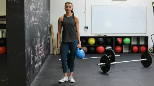 Confident woman holding kettlebell by wall in gym