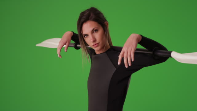 Confident woman in wetsuit holding kayak paddle over shoulders on greenscreen