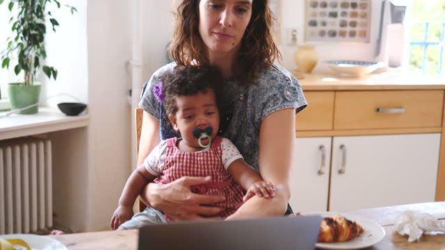 confident woman using laptop while sitting with daughter at table - ein elternteil stock-videos und b-roll-filmmaterial