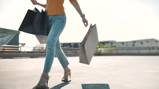 confident woman walking with shopping bag in the shopping center - bag stock videos & royalty-free footage