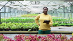 Confident woman with digital tablet in greenhouse