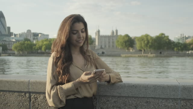 confident young adult business woman using smart phone and commuting in city, independent female executive successful corporate career - working remote location stock videos & royalty-free footage