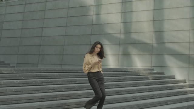confident young adult business woman using smart phone commuting in city, independent female executive moving up successful corporate career ladder - indian ethnicity stock videos & royalty-free footage