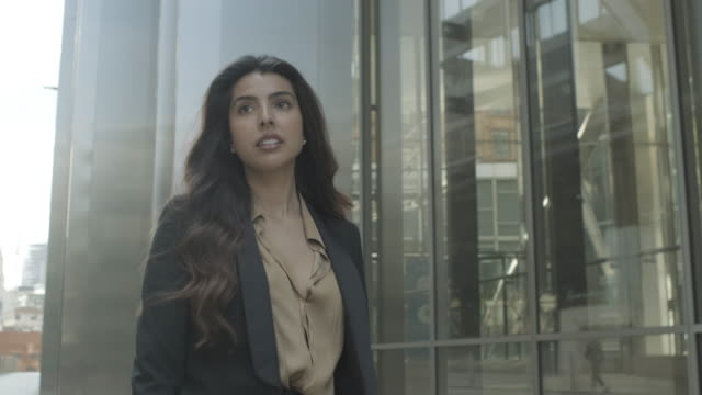 confident young adult business woman walking in city leaving office wearing suite, independent female executive successful corporate career - waist up stock videos & royalty-free footage