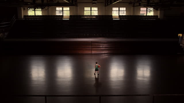 A young basketball player walks to the center court line in an empty basketball gym.