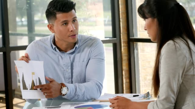 confident young businessman discusses financial bar chart with female colleague - etnia latino americana video stock e b–roll