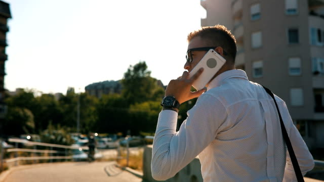 Confident young businessman using cell phone in city