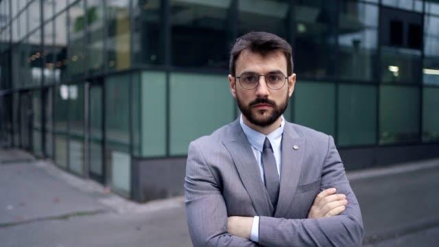 vidéos et rushes de jeune homme d'affaires confiant - visage sans expression