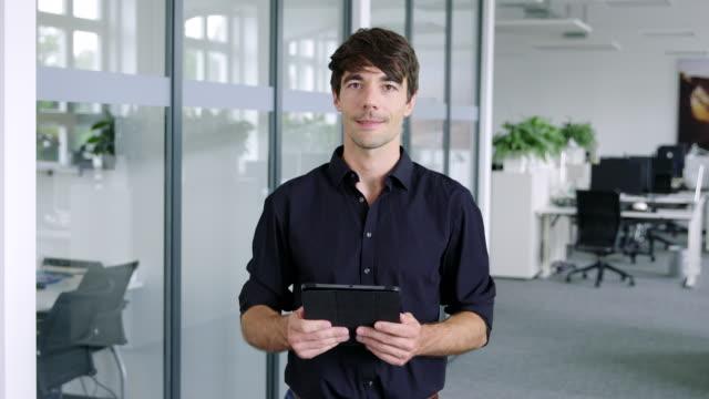 selbstbewusster junger geschäftsmann mit digitalem tablet - oberkörper stock-videos und b-roll-filmmaterial