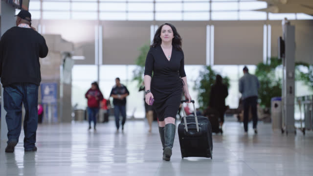 slo mo. confident young businesswoman rolls suitcase through airport terminal. - wheeled luggage stock videos & royalty-free footage