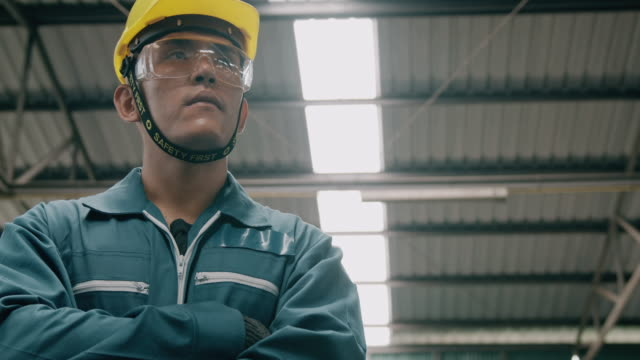 confident young industrial worker portrait, arm cross, look at camera and look up view. slowmotion, asian male, overalls, helmets. industrial and manufactory concept. - non us location stock videos & royalty-free footage