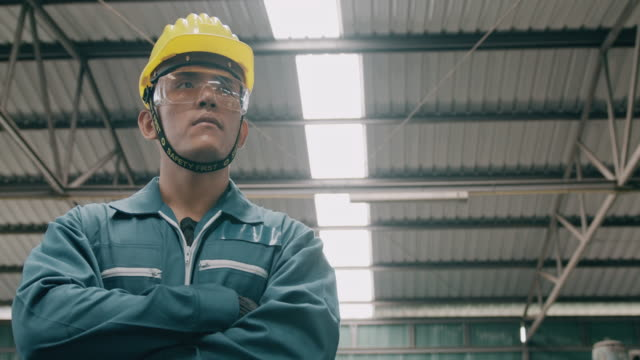 vidéos et rushes de verticale confiante de jeune ouvrier industriel, croix de bras, vue de regard. slowmotion, mâle asiatique, salopettes, casques. concept industriel et manufactory. - manufacturing occupation
