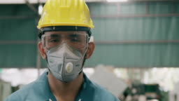 Confident young industrial worker portrait, wearing mask, close up. Slowmotion, Asian male, overalls, helmets. Industrial and manufactory concept.