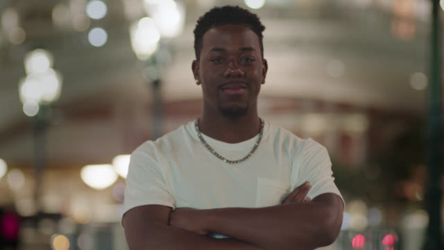 ms. confident young man crosses his arms and smiles at camera on las vegas strip at night. - las vegas crosses stock-videos und b-roll-filmmaterial