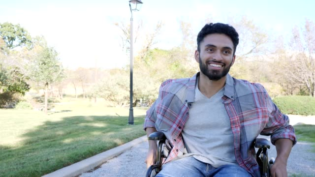 confident young man pushes himself in wheelchair on path - orthopedic equipment stock videos & royalty-free footage