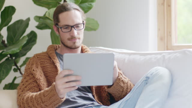 confident young man with digital tablet on sofa - houseplant stock videos and b-roll footage