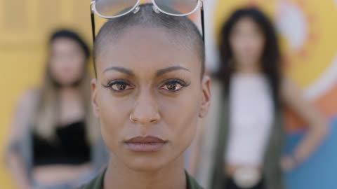 vidéos et rushes de cu slo mo. confident young mixed-race woman looks up and stares at camera while two women stand out of focus in background. - endurance