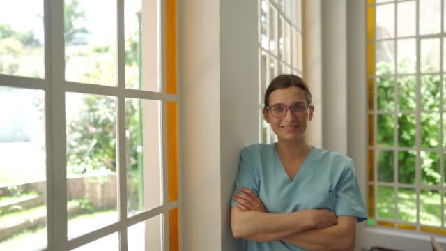 vídeos de stock e filmes b-roll de confident young nurse in uniform with crossed arms - enfermeira