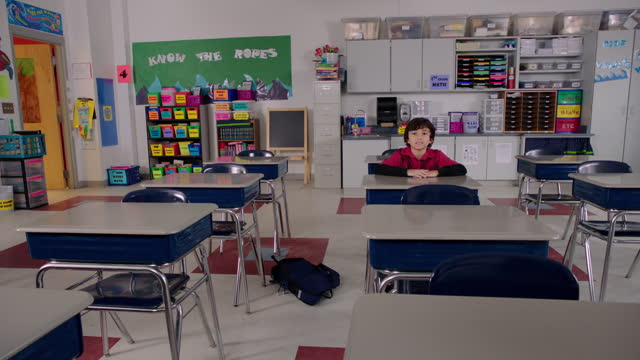 A confident young student walks into class and takes a seat at his desk.
