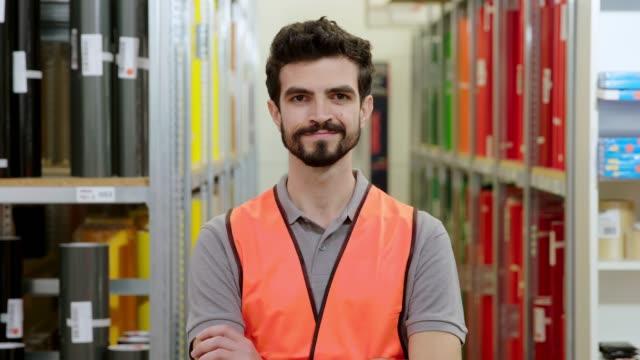 confident young warehouse worker - braccia incrociate video stock e b–roll