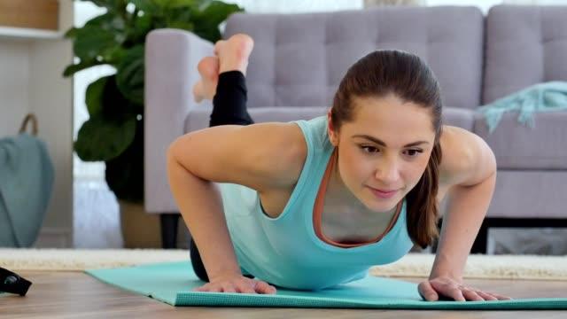 自信を持って若い女性は家で腕立て伏せを膝します。