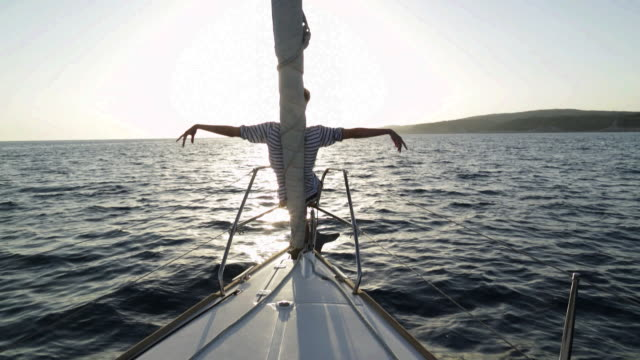 confident young woman sitting at bow of yacht leaning against jib enjoying the breeze and mimicking waves with her arms. - lehnend stock-videos und b-roll-filmmaterial