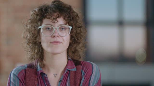 vidéos et rushes de slo mo cu confident young woman smirks as she looks into the camera - détermination