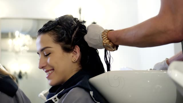 Confident young woman uses smartphone in hair salon