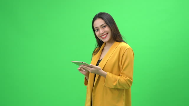 confident young woman using digital tablet looking at camera - green background stock videos & royalty-free footage